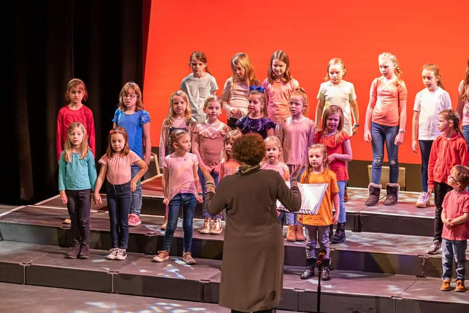 Jessa in a long green jacket, conducting a brightly coloured choir of children from Wigginton Singstars