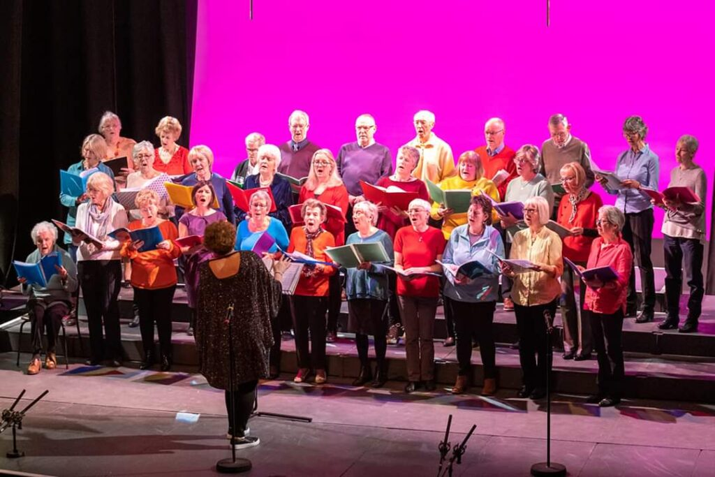 Jessa, dressed in a sparkly dress, conducting the brightly coloured Easingwold Community Singers at the Joseph Rowntree Theatre, York,