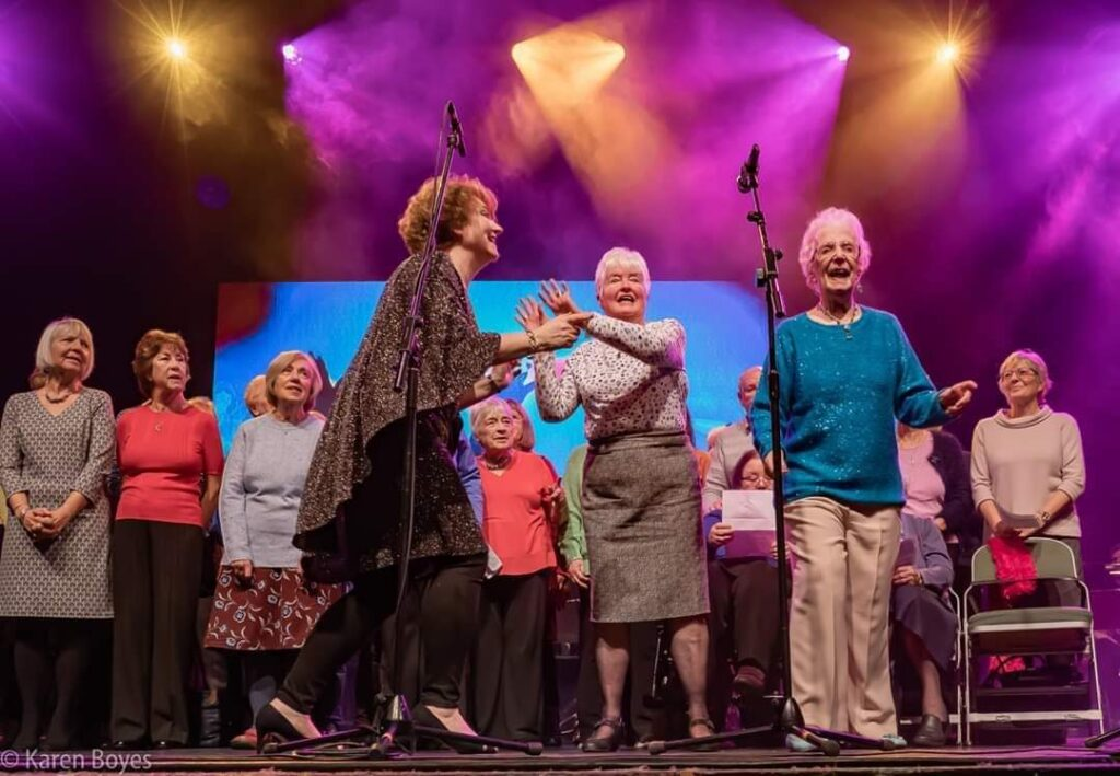 Jessa is singing with SInging For All on the York Barbican stage, with two ladies at the front singing solos, dancing and clapping along.