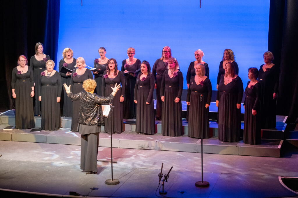 Jessa conducting the York Military Wives Choir, all dressed in black evening wear, at the Joseph Rowntree Theatre York