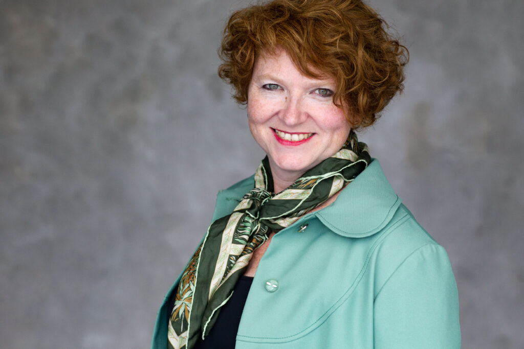 Jessa wearing a pale green jacket and patterned scarf, smiling at the camera.